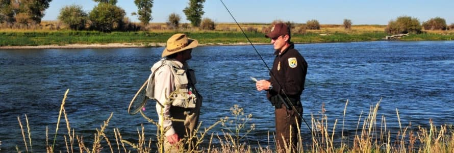 A ranger with the U.S. Wildlife & Fish Service speaks with a fisher alongside a river in the Seedskadee National Wildlife Reserve