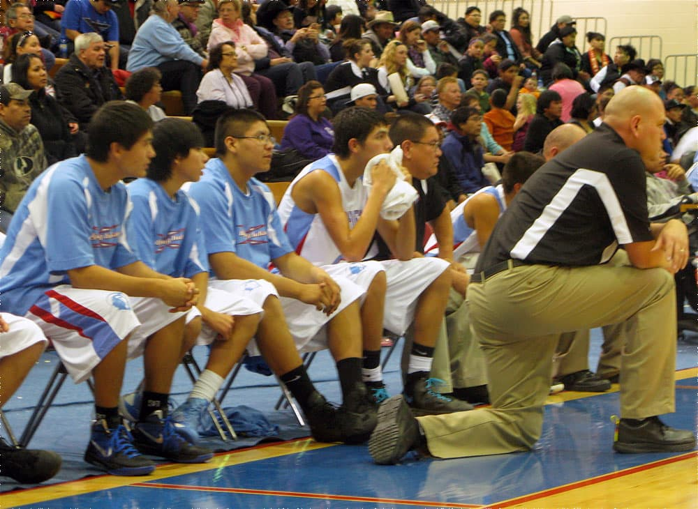 Coach Craig Ferris and his bench players follow the action on Friday night