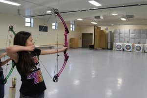 Skye Sanderson, 10, takes aim at a target. Students at Wind River Elementary are competing in the state's virtual archery tournament. (Kelsey Dayton- Wyofile)