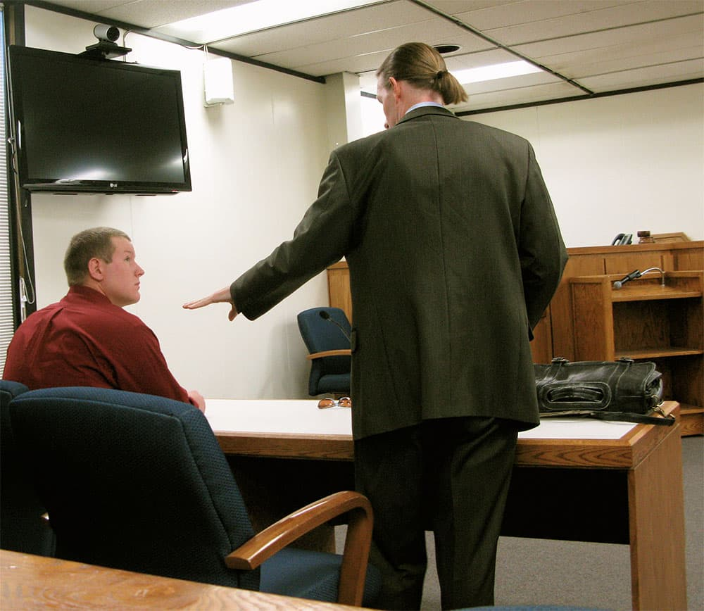 James Crooks listens to his lawyer, Scott Stinson, before the hearing begins on May 27.