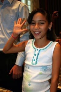 A young immigrant raises her right hand during a naturalization ceremony in Los Angeles. Many DACA enrollees came to the U.S. at a young age and don't know how to speak Spanish. Unlike this girl, they are unable to enter the naturalization process.