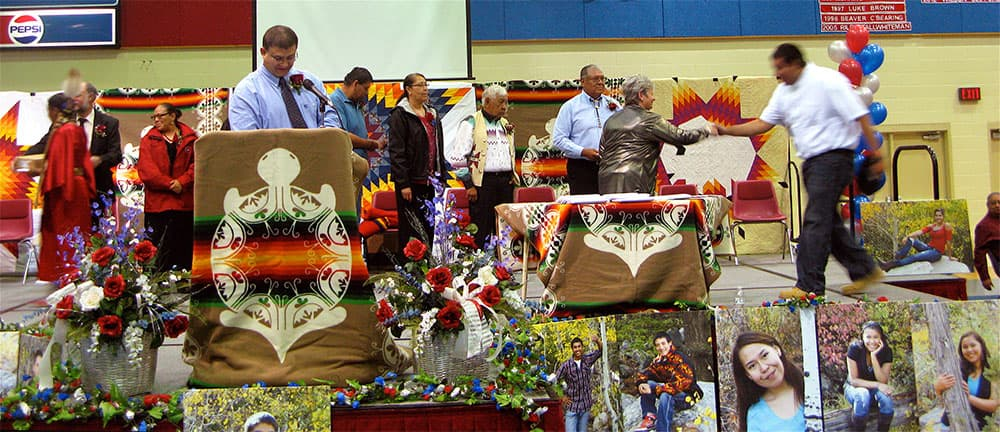 Stephen Headley rushes to receive his diploma and shake hands with Superintendent Michelle Hoffman as Principal Phil Garhart reads the names of the 2013 Wyoming Indian graduates.