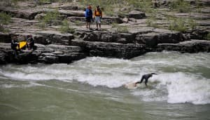 "Brian Fox surfs ""Lunch Counter"" a rapid on the Snake River while kayakers and other surfers look on. (Kelsey Dayton/Wyofile)"