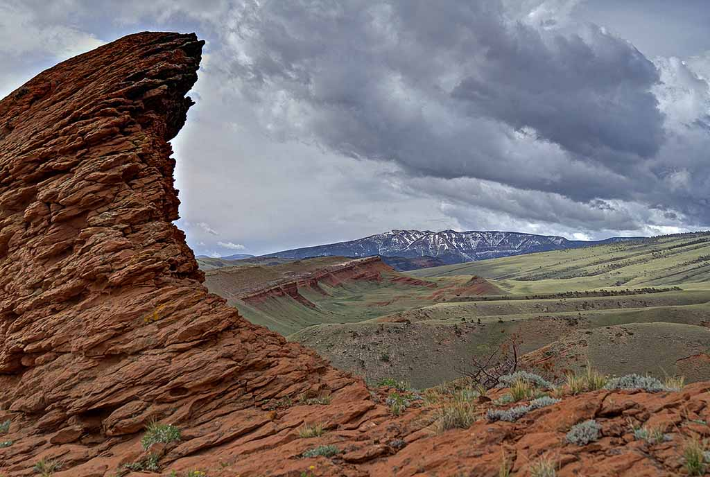 A red clay outcropping dramatically frames the view near Bald Ridge in Park County, Wyo. (Kathy Lichtendahl/Flickr - click to enlarge)