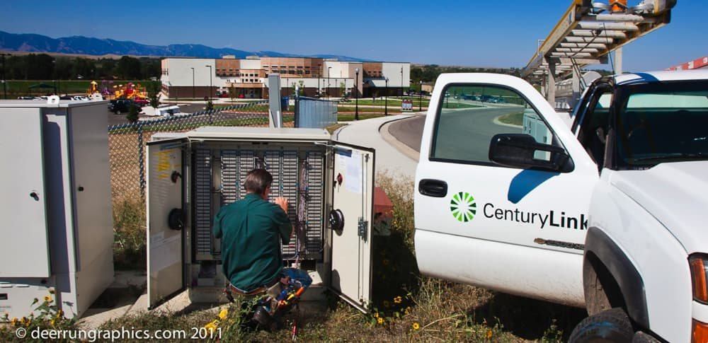 A CenturyLink employee works on communications equipment outside a school campus in Sheridan County. Since June of 2013, Phase I of the Wyoming Broadband Initiative has increased data speeds at public schools by an average of 700 percent across the state. (Courtesy Deer Run Graphics/Stan Woinoski  — click to enlarge)