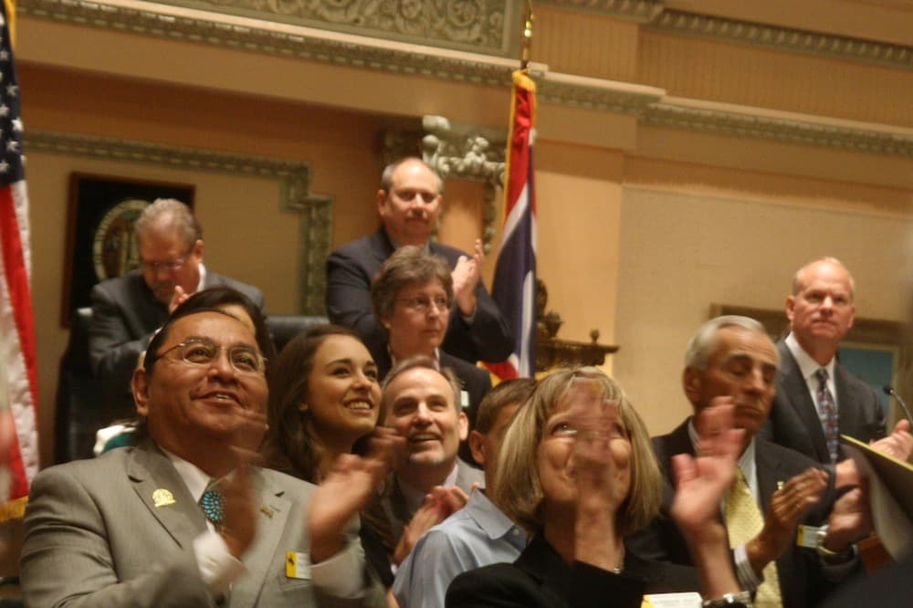 Rep. Patrick Goggles (D-Ethete), bottom left, applauds dignitaries from the Wind River Reservation at the opening of the 2014 budget session. Sen. Eli Bebout (fifth from left) and Gov. Matt Mead (far right). (WyoFile/Gregory Nickerson — click to enlarge)