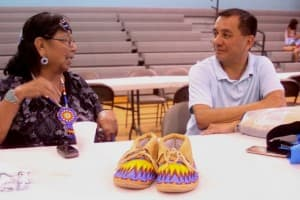 Joanna Tillman talks with beadworker John Timbana, who grew up  partly in Fort Washakie but now lives in Nevada. (Gregory Nickerson /  WyoFile — click to enlarge)