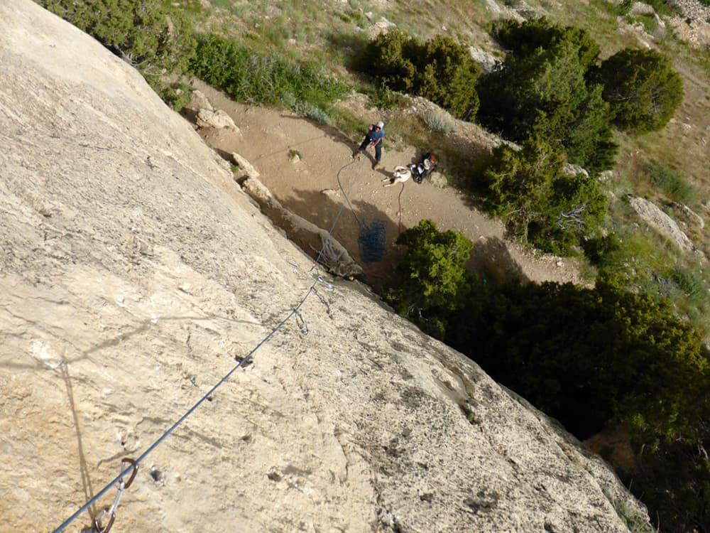 Dog and belayer at the bottom of a sport climb in Sinks Canyon. Photo by Emilene Ostlind