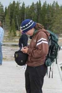 Mara Reed, 18, takes notes while waiting for a geyser to erupt. Reed, a geyser gazer from Minnesota, spent several weeks in Yellowstone National Park this summer, almost all of it in the upper geyser basin, where she watched and recorded eruptions. (photo by Kelsey Dayton - click to enlarge)