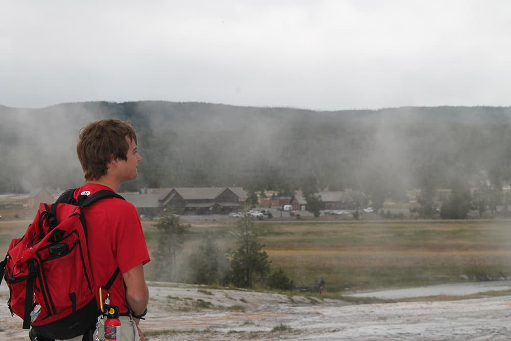 Ryan Maurer looks out across the geyser basin looking for tells of which geysers might be preparing to erupt. Much of geyser gazing is waiting, even when one does know what signs signal and eruption, he said. (photo by Kelsey Dayton - click to enlarge)