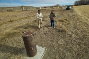 John Fenton and a neighbor in Pavillion visit the site of a monitoring well drilled to help determine the source of pollution in residents' water wells. (Angus M. Thuermer Jr./WyoFile — click to enlarge)