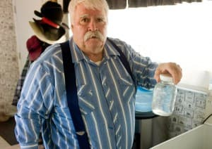 Pavillion resident Louis Meeks holds a jar of his tap-water that smells like diesel fuel. Pollution crept into his well and when he tried to drill another, it blew out from underground pressure he believes came from nearby gas operations. (Angus M. Thuermer Jr./WyoFile)