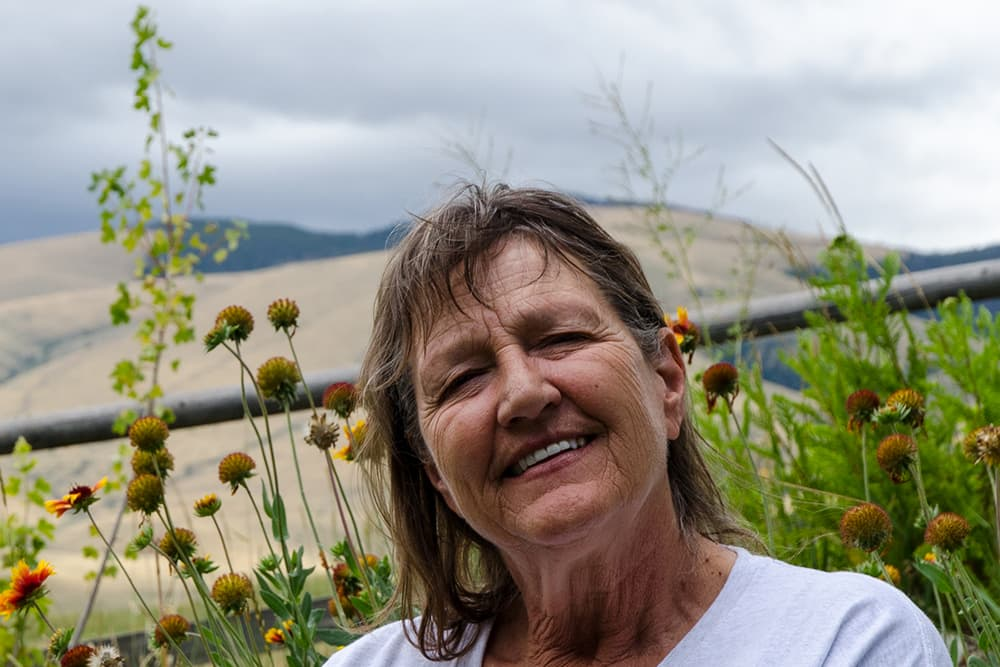 Karen King, outside her rural Ft. Washakie home. The longtime Wyoming resident had a long and productive career in education. She holds an advanced degree and elected office but is excluded from medical insurance coverage thanks to Wyoming's Medicaid gap. (Matthew Copeland/WyoFile)