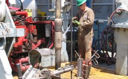 A worker sprays a jointon a rig drilling an unconventional natural gas well in BP America's Wamsutter field in Wyoming. OSHA issued a hazard alert this month warning of dangerous toxins associated with hydraulic fracturing activities. (Dustin Bleizeffer/WyoFile)