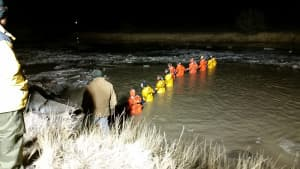 Specially-trained ice rescue volunteers form a line in a grid-style search on the night of Feb. 8 in the Powder River. (courtesy Johnson County Search and Rescue)