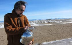 University of Wyoming atmospheric sciences professor Dr. Robert Field uses a canister to collect an air sample as part of a spatial air quality assessment in the Pinedale Anticline in 2013. (Dustin Bleizeffer/WyoFile)