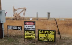 "Signs warn of dangers related to an oil production facility outside Cheyenne. Some Cheyenne-area homeowners are not satisfied with the state's new ""setback"" rule to buffer nuisances and dangers of oil and gas activities from residential areas. (Photo courtesy of Jill Morrison)"