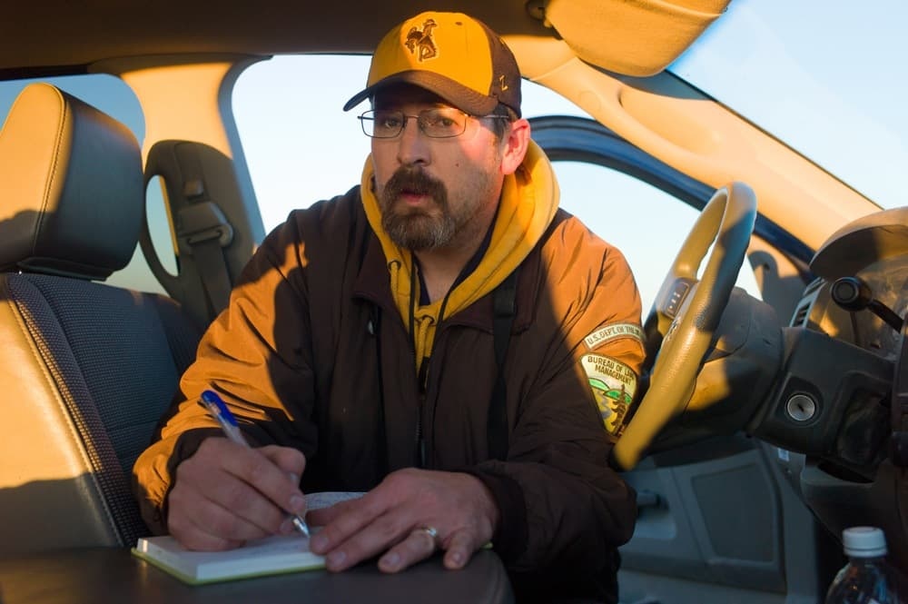 BLM biologist Dale Woolwine and a colleague discovered sites where wintering grouse peck at dirt, documenting a winter activity known as geophagia. At dawn one day last week south of Pinedale, he enters a count of strutting grouse in his notebook. Angus M. Thuermer Jr./WyoFile)