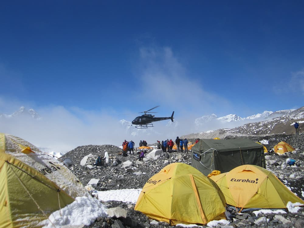 A helicopter ferries those who survived an earthquake and subsequent avalanches on Mount Everest, off the mountain. (courtesy Darren Rogers)