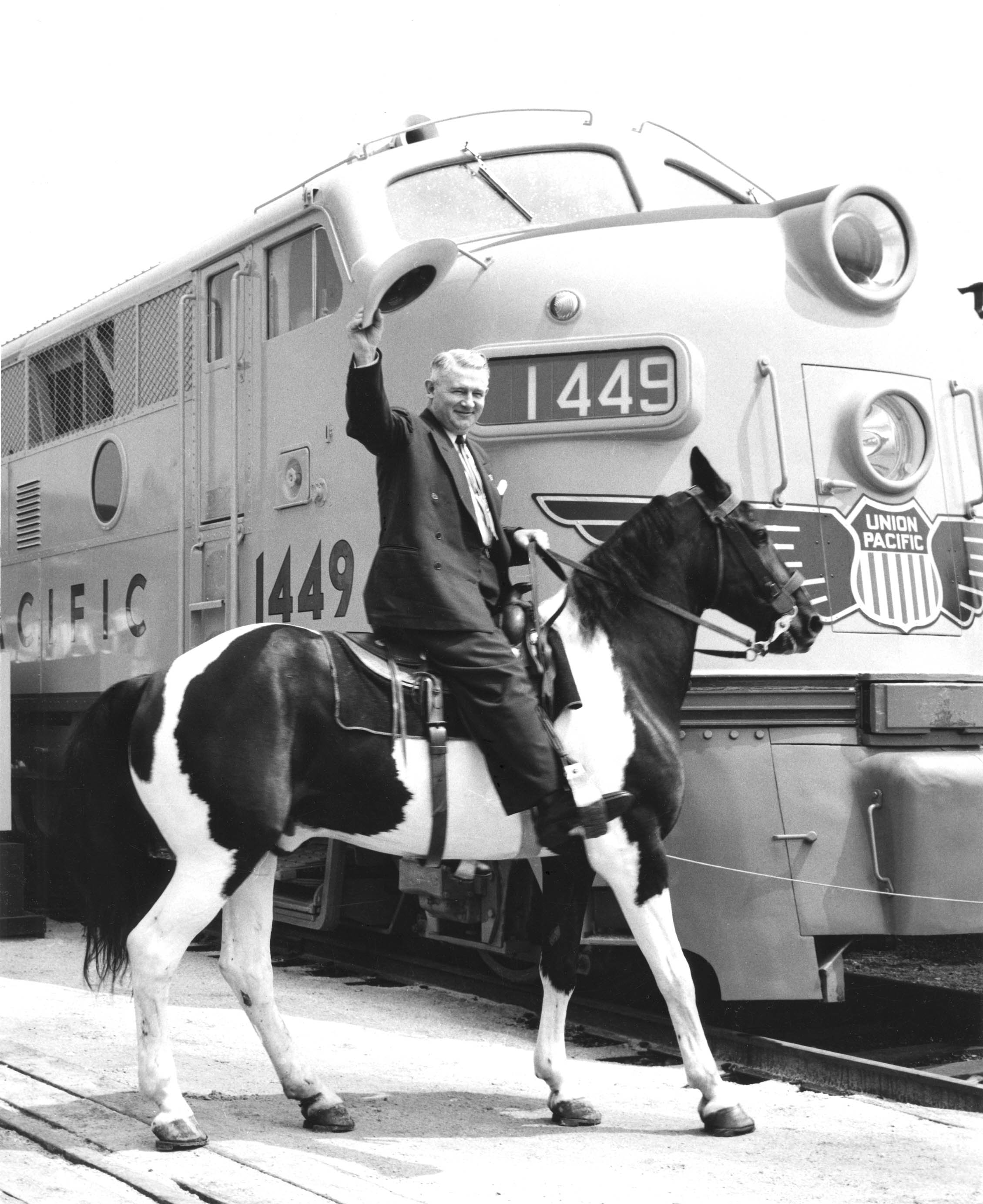 Lester Hunt rides a pinto horse next to a Union Pacific engine, in 1945.