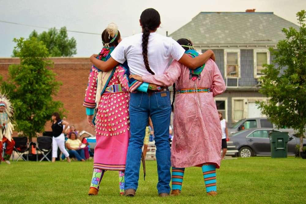 """Crow dancers participate in a round dance during the First People's Powwow at the Sheridan Inn on Thursday. Round dances are considered """"social"""" and invite men and women to dance together, often with audience members joining in. (Gregory Nickerson/WyoFile)"""
