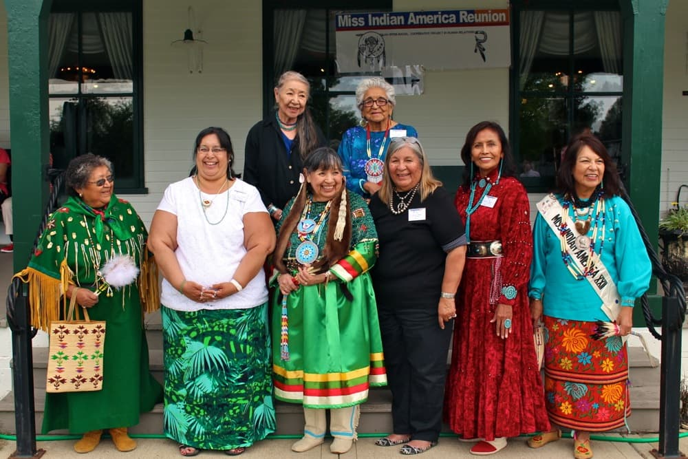 The Sheridan Inn hosted the Miss Indian America reunion on Thursday, after an initial event in 2013. FRONT ROW: Arlene Wesley (Yakima), Miss Indian America 1953; daughter representing Brenda Bearchum (Northern Cheyenne-Yakima), MIA 1961; Williamette Youpee (Sisseton-Yankton Sioux), MIA 1963; Sharon Ahtone Harjo (Kiowa) MIA 1965; Sarah Johnson Luther (Navajo) MIA 1967; Deana Harragarra Waters (Kiowa-Otoe), MIA 1976. BACK ROW: 1954 Miss Indian America runner-up Annie Grace Strange Owl (Northern Cheyenne); Jewel Medicine Horse Williams (Crow), secretary to Howard Sinclair, founder of Miss Indian America pageant and All-American Indian Days. (Gregory Nickerson/WyoFile)