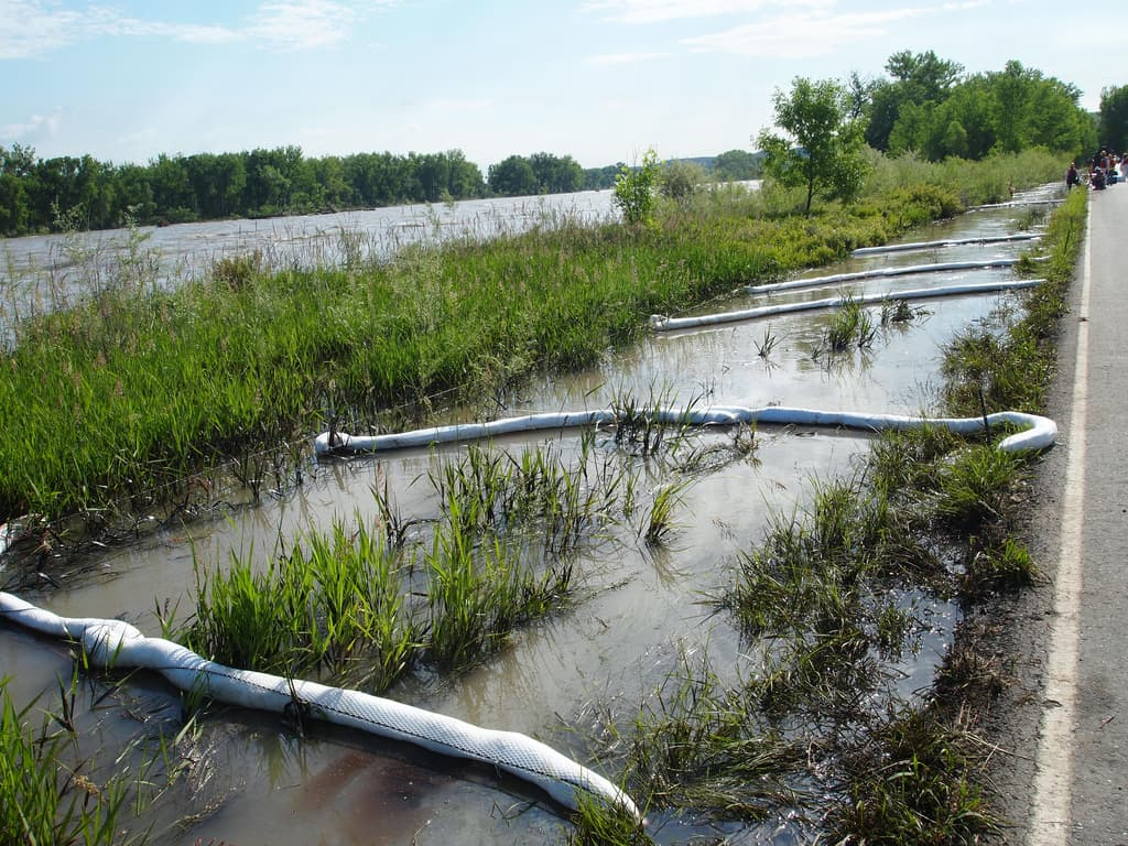 Booms collect oil from the 2011 Silvertip spill along Thiel Rd in Laurel, MT. Most of the oil — and cleanup — was concentrated on this roughly 1 mile stretch of road that runs alongside the river. (Tom Bearden/Flickr Creative Commons)