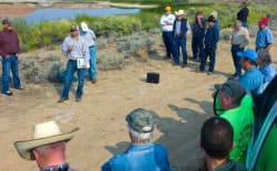 Wyoming would expand the Upper Leavitt Reservoir near Shell at a cost of $41 million. Much of the area's landscape would be arid without irrigation like that supplied by the reservoir behind participants in a Wyoming Water Development Office tour. Jason Mead, deputy director for the dam and reservoirs section, addresses the group. (Angus M. Thuermer Jr./WyoFile)