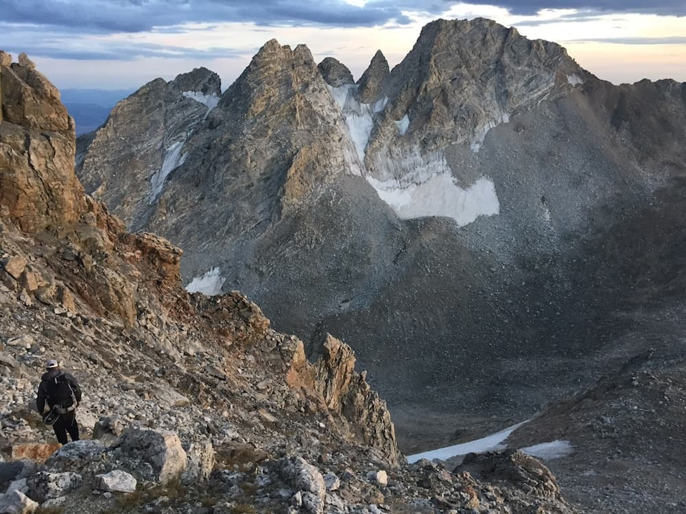 """Ryan Burke descends from the Middle and South Tetons, with Ice Cream Cone, Spalding Peak, Gilkey Tower and Cloudveil Dome in the background, during what he called the """"Perception Traverse,"""" a four-day crossing of the range with summits on 24 peaks. (courtesy Taylor Luneau)"""