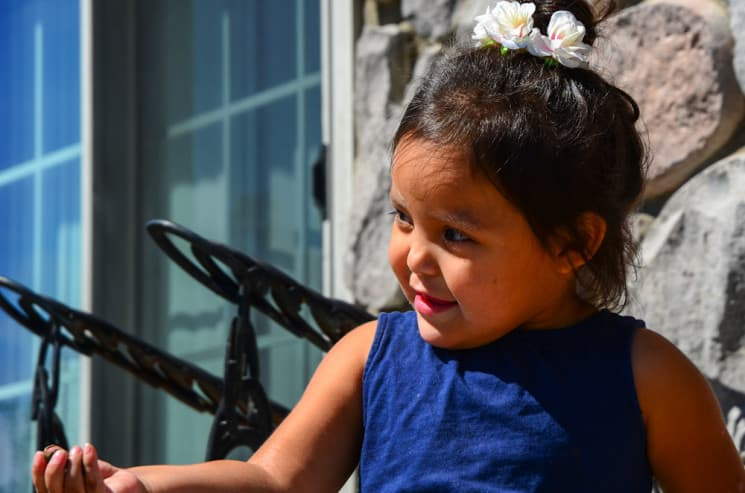 Amarie Swallow enjoys the sunshine and the carefree life of a toddler on her grandparents' front porch outside of Fort Washakie. Her family works hard to ensure that her future is equally bright, but hidden dangers lie ahead. (photo by Matthew Copeland/WyoFile)