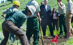 U.S. Secretary of Agriculture Tom Vilsack visits a trail crew working on the Bridger-Teton National Forest this summer. Similar programs and other forest work scheduled for the fall had to be cancelled when the cost of fighting fires required borrowing their funding. (Angus M. Thuermer Jr.WyoFile)