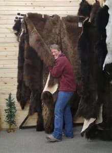 "Barb Heinze hugs a buffalo hide in Merlin's Hide Out, the shop she owns with her husband, Merlin. The shop is known for its buffalo hides and built the coats worn by Kurt Russell in the movie ""The Hateful Eight."" (courtesy)"