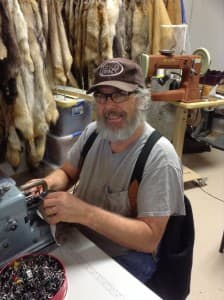 "Merlin Heinze sews a buffalo hide into a coat for the movie ""The Hateful Eight."" (courtesy)"