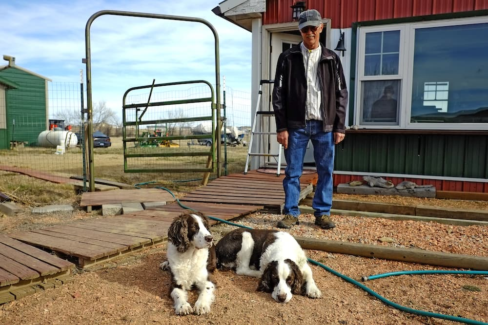 """Frank Latta takes a break from fixing a light outside his home with his bird dogs Tess, left, and Button. After serving as Gillette's mayor and as a Wyoming legislator, he is now trying to get a medical marijuana ballot measure before voters in the fall of 2017. Afflicted by MS, """"it's OK for me to get hooked on heroin,"""" Latta says, """"but it's not OK for me to take a derivative of cannabis."""" (Ed Glazar/Gillette News Record)"""