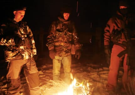 Self-described patriots gathered around a fire to keep warm, after they occupied the headquarters of the Malheur National Wildlife Refuge. A federal review says such conflicts are partly responsible for agencies not knowing the extent of unauthorized grazing. (Brooke Warren/High Country News)