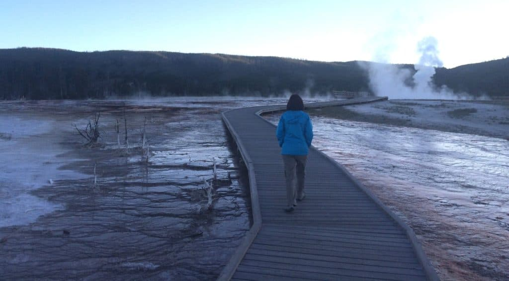 Kristin Maxwell walks along a boardwalk in Yellowstone National Park in June. Even at the end of June, popular sites like Biscuit Basin are almost deserted in the evening. (Kelsey Dayton/WyoFile)