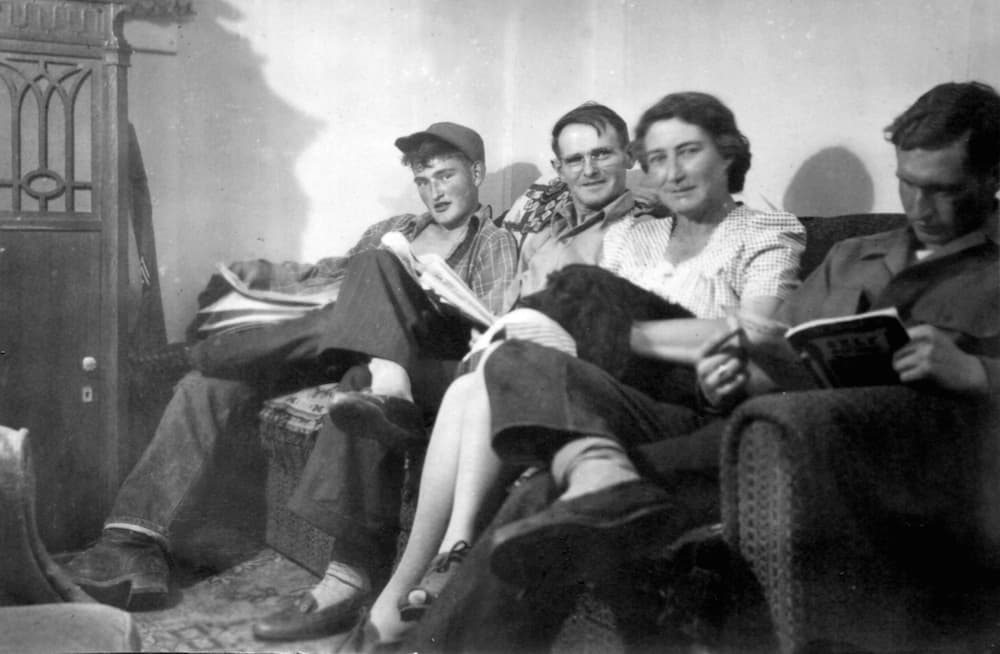 "From left: Lafayette ""Bud"" Bell, Lafe Bell, Hilda Bell and Tom Bell read on the couch at their home in Lander. The Bell family were readers, something Tom Bell continued to do until his death. (Photo courtesy Matt Winters)"