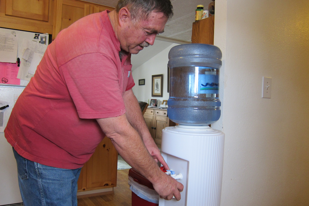 In this file photo, Jeff Locker uses bottled water at his house near Pavillion, where residents have little faith in a state study that could not link water problems to nearby fracking. (Dustin Bleizeffer/WyoFile)