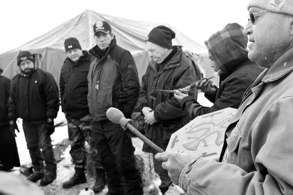 Veterans gave rare permission to photograph a ceremony before they embarked on a march demonstrating against the pipeline construction. Bitter cold, a blizzard, and limited supplies forced many of them to leave the camp before they planned. (Angus M. Thuermer Jr./WyoFile)