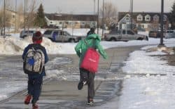 Two boys hurry to Sunrise Elementary School in Cheyenne on Monday, the future of their education facing uncertain financing. The Legislature  has a challenge to fund schooling in the face of a decline in mineral revenue. (Andrew Graham/WyoFile)