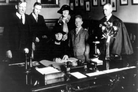 Nellie Tayloe Ross signing her oath of office as governor of Wyoming on Jan. 5, 1925. Behind her are, from left; Judge Samuel Tayloe, her brother;  George Ross, her son; Mrs. Alfred Tayloe, her sister in law; William Bradford Ross, her youngest son; and Wyoming Supreme Court Chief Justice C.N. Potter, who administered the oath of office. (Wyoming State Archives)