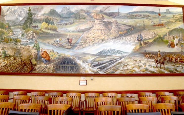 """Painted in 1980 by Mike Kopriva, the mural """"Wyoming, the Land, the People"""" hangs in a committee room in the Wyoming State Capitol. It's a large-scale depiction of Wyoming people and places, with one notable exception — there are no Native Americans and only a minor archaeological reference to their existence. (Rachel Girt/Capitol Square Project)"""