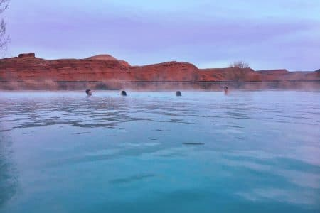 A group of friends enjoy warm water and an unseasonably warm evening in a hot spring on the edge of Thermopolis on Feb. 19 (Sophia Jensen)