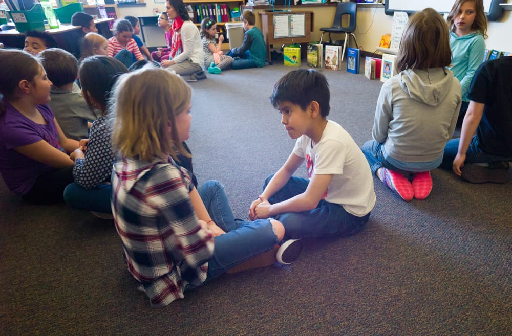 In Natalie Lyon's third grade class at John Colter Elementary school in Jackson on Monday, students discuss the theme of a story during a literature exercise. Lyon had an assistant who helped students learning English as a second language. (Angus M. Thuermer Jr/WyoFile)